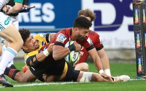 Crusaders Richie Mo'unga Scores a try with Hurricanes' Ardie Savea holding on.