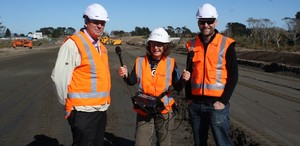 Graham Blick (left), Chief Geodesist at LINZ, and survey manager Will Newall (right), with Alison Ballance at the construction site of the MacKays to Peka Peka expressway.