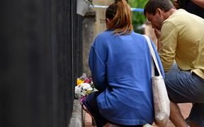 People leave flowers at a police cordon at the Abbey Gateway near Forbury Gardens park in Reading, west of London, on June 21, 2020 following a fatal stabbing incident the previous day. -