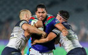 Warriors forward Tohu Harris tries to break through two North Queensland tacklers.