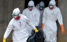 Medical workers of the Liberian Red Cross carry the body of a victim of the Ebola virus in a bag on 4 September.