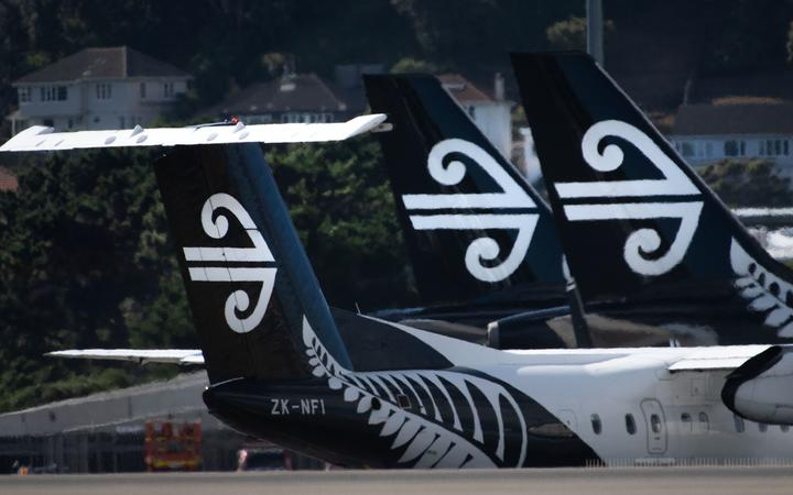 Air New Zealand airplanes wait for passengers outside the international terminal as a plane taxis (L) at Wellington International airport on February 20, 2020.