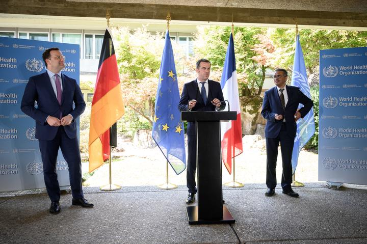 French Health Minister Olivier Veran speaks, flanked by German Health Minister Jens Spahn (left), and WHO Director-General Tedros Adhanom Ghebreyesus.