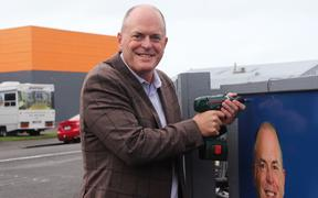 Todd Muller places the final screw in the new billboard in Napier