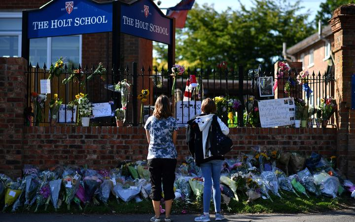 People look at floral tributes left outside The Holt School in Wokingham on June 23, 2020 in memory of teacher James Furlong who was a victim in the knife attack in Reading which killed three people. -
