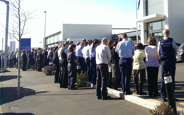 Police staff observe two minutes silence outside Christchurch Central Police Station.