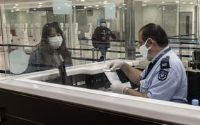 A passenger wearing a mask waits with her documents at passport control at Larnaca International Airport, 9 June  2020.