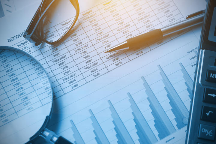 Accounting business documents with calculator, pen, glasses and magnifying glass.  The concept for finance