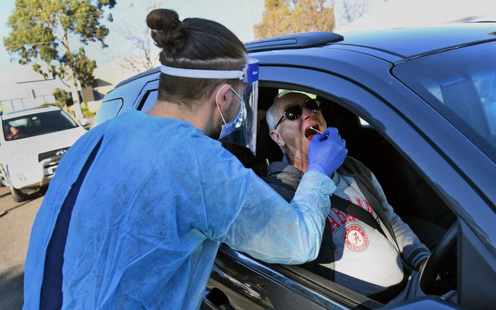 A man has a swab sample taken during testing for the COVID-19 coronavirus at a drive through pop-up venue in Melbourne on July 1, 2020.