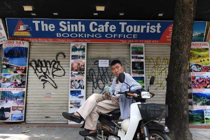 A motorcycle taxi rider waits for customers in front of a tourist office, closed due to the current COVID-19 novel coronavirus situation, in Hanoi.