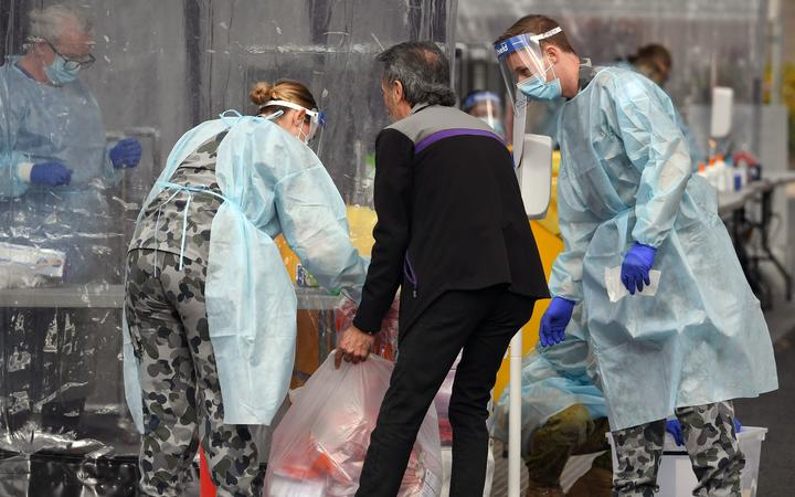Members of the Australian Defence Force package swab samples ready for testing at a drive-through COVID-19 coronavirus testing station in the Melbourne suburb of Fawkner on July 2, 2020.