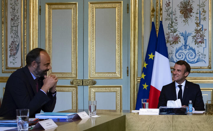 French President Emmanuel Macron (R) chats with French Prime Minister Edouard Philippe during a meeting.