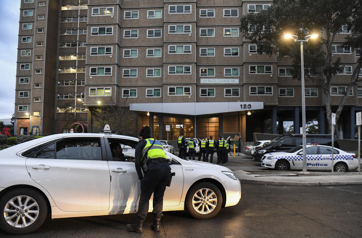 Police gather outside one of nine public housing estates which have been locked down in Melbourne.