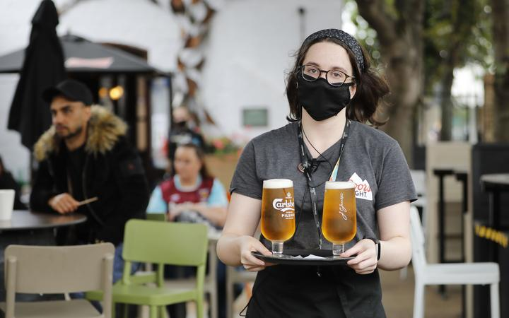 A member of bar staff wearing PPE (personal protective equipment) in the form of a face mask, serves customers with drinks outside the Wetherspoon pub, Goldengrove in Stratford in east London on July 4, 2020, as restrictions are further eased during the novel coronavirus COVID-19 pandemic.
