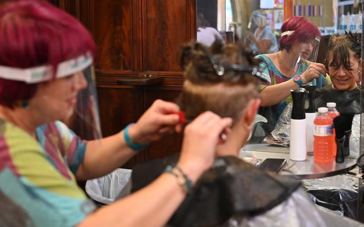 A hair stylist wears a PPE facemask as she works at a hair salon in Birkenhead, north west England on July 4, 2020. -