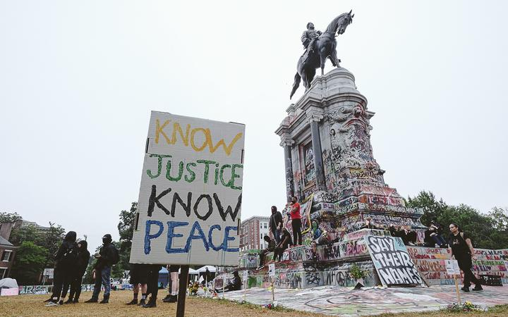 RICHMOND, VA - JUNE 20: A No justice no peace sign stands at the Robert E. Lee monument on June 20, 2020 in Richmond, Virginia.