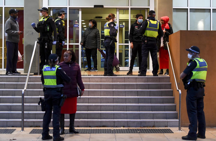 Police speak to residents of one of the nine public housing estates locked down in Melbourne.
