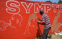 Liberian street artist Stephen Doe paints a mural in Monrovia to inform people about the symptoms of Ebola.