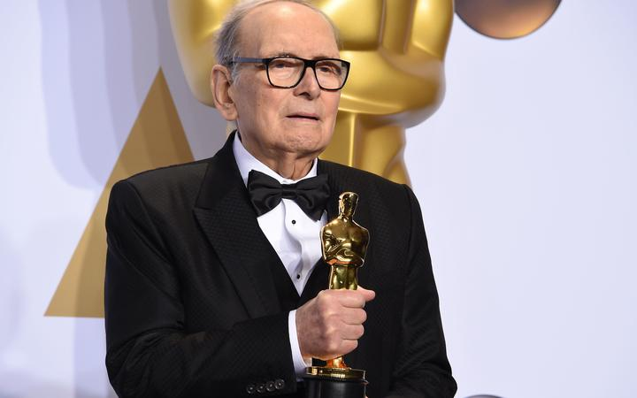"""(FILES) In this file photo taken on February 28, 2016 Italian composer Ennio Morricone poses with the Oscar for Best Original Score, """"The Hateful Eight,"""" in the press room during the 88th Oscars in Hollywood."""