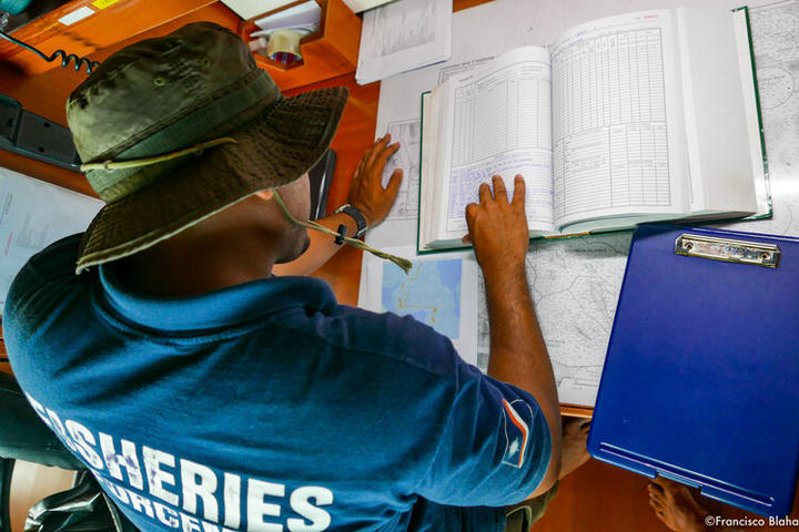 A Marshall Islands Marine Resources Authority officer crosschecks for suspicious vessel behaviours identified in the Vessel Monitoring System (map on the lower left) with Logbooks, catch logsheets, temperature records, etc. found on board.