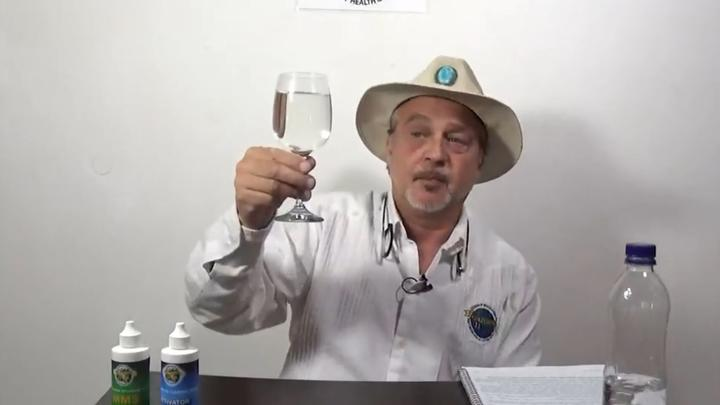 Mark Grenon holds a glass containing chlorine dioxide bleach and water, which he calls Miracle Mineral Solution