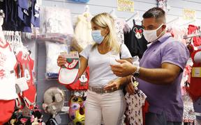 LAKE BUENA VISTA, FL - JULY 08: Nikki Hastings (L) and Carlos Aguilera Gift Shop for Disney apparel for relatives at the LBV Gift Shop on July 8, 2020 in Lake Buena Vista, Florida.