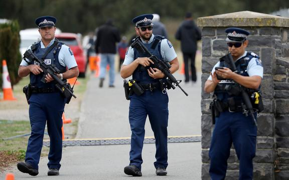 Armed police officers stand guard during the burial ceremony of the victims killed in Christchurch's mosque attacks at the Memorial Park Cemetery in Christchurch, New Zealand on March 21, 2019.