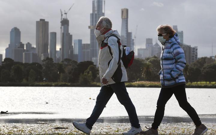 People walk along Albert Park lake in Melbourne on July 13, 2020, as five million people in Australia's second-biggest city began a new lockdown following a resurgence of coronavirus cases.
