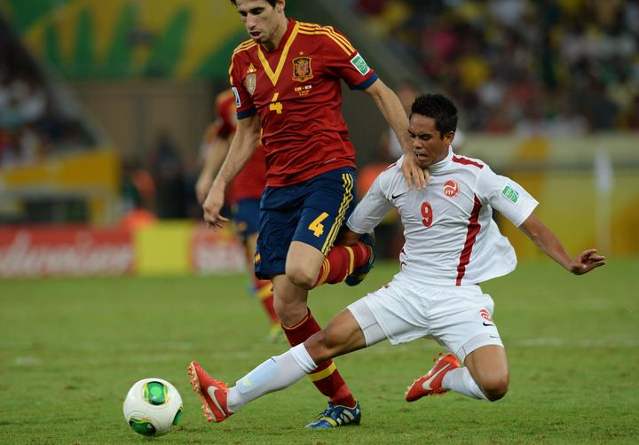 Tahiti's Teaonui Tehau looks to dispossess Spain midfielder Javier Martinez during the 2013 FIFA Confederations Cup in Brazil.