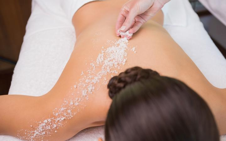 Beauty therapist pouring salt scrub on womans back in the health spa