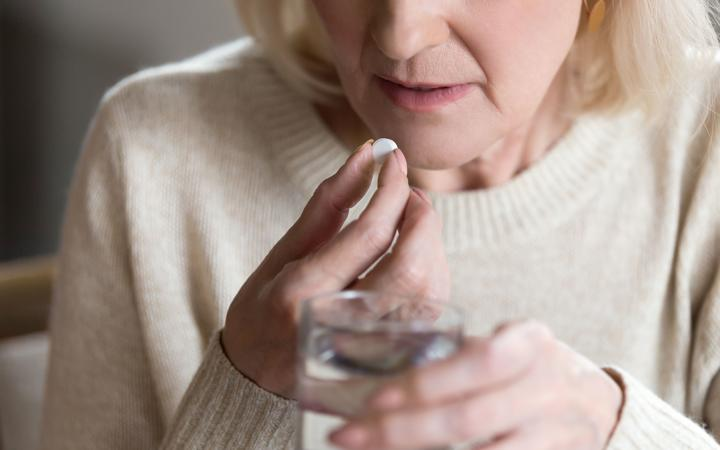 Close up of unhealthy middle aged woman suffers from pain, holding pill and glass of still water feels ill taking medicine, cropped image.
