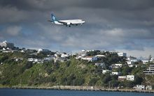 A Boeing 737 descends over Evans Bay to land at Wellington International Airport.