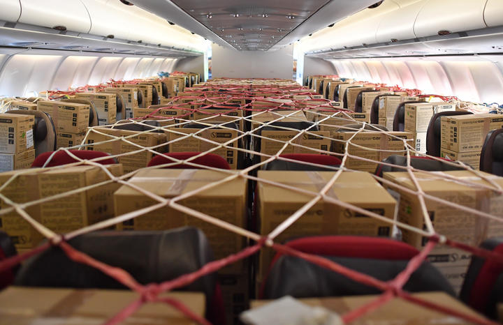Cargo nets cover boxes of PPE stored on passenger seats inside the cabin of an aircraft, after it landed at Bournemouth Airport in southern England on May 6, 2020(Photo by Ben STANSALL / AFP)