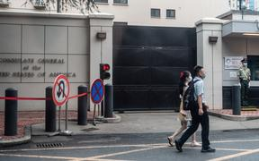 People walk past the entrance of the US consulate in Chengdu, southwest China's Sichuan province. China ordered the consulate's closure in retaliation after the US shuttered Beijing's diplomatic mission in Houston.