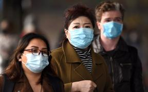 Commuters walk outside Melbourne's Flinders Street Station on July 23, 2020 on the first day of the mandatory wearing of face masks in public areas as the city experiences an outbreak of the COVID-19 coronavirus.