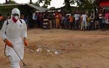 A Liberian Red Cross health worker  disinfects a courtyard  after the body of a victim of the Ebola virus was found.