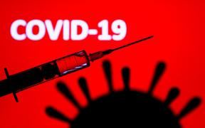 Coronavirus model and medical syringe are seen with 'covid-19' sign displayed on a screen in the background in this illustration photo taken in Poland on June 9, 2020.