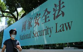 A man walks past a government public notice banner for the National Security Law in Hong Kong, 15 July 2020