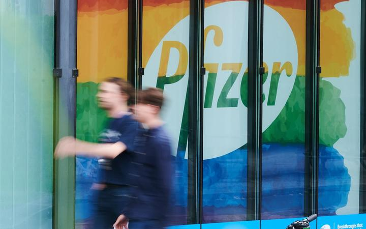 28 July 2020, Berlin: Passers-by walk in front of a building of the Pfizer Deutschland GmbH headquarters. Pfizer will publish figures for the 2nd quarter on Tuesday. Photo: Annette Riedl/dpa
