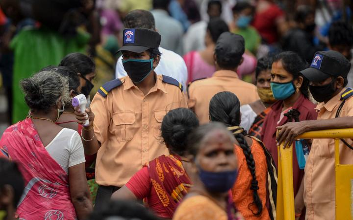 A security personnel (C) checks the body temperature of a woman (C-L) as she enters a market as a preventive measure against the spread of the COVID-19 coronavirus in Chennai on July 29, 2020.