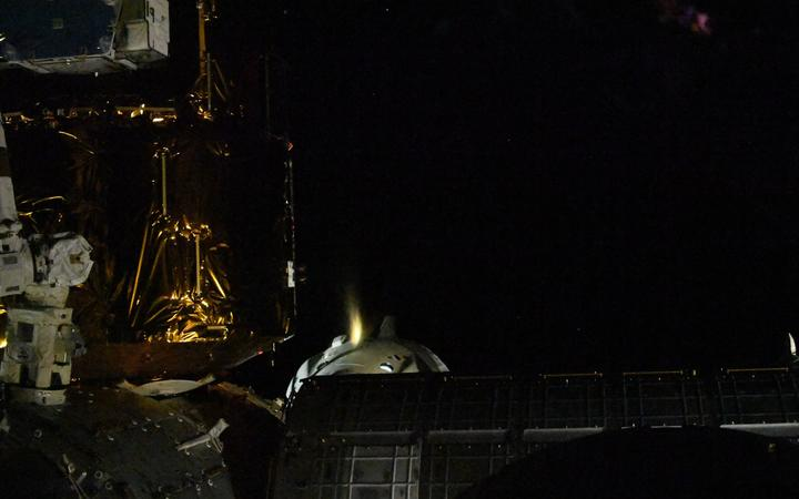 This handout picture released courtesy of NASA shows SpaceX Crew Dragon Endeavour firing one of its thrusters to back away from the International Space Station photographed by Space Station Commander Chris Cassidy on August 1, 2020.