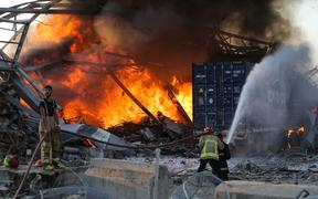 Firefighters douse a blaze at the scene of an explosion in Beirut's port district.