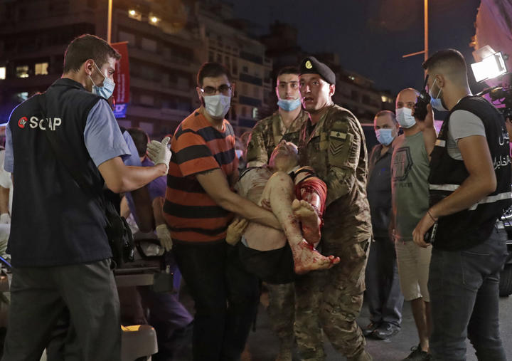Lebanese army soldiers carry away an injured man at a hospital in the aftermath of an explosion at the port of Lebanon's capital Beirut on August 4, 2020.