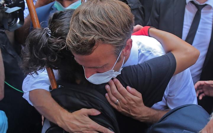A Lebanese youth hugs French President Emmanuel Macron during a visit to the Gemmayzeh neighborhood, which has suffered extensive damage due to a massive explosion in the Lebanese capital, on August 6, 2020. - French President Emmanuel Macron visited shell-shocked Beirut,
