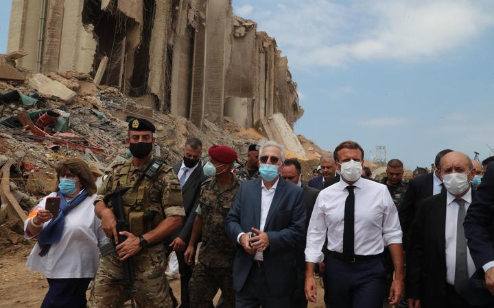 A handout picture provided by the Lebanese photo agency Dalati and Nohra on August 6, 2020, shows French President Emmanuel Macron (2nd-R) and Foreign Minister Jean-Yves Le Drian (R) inspecting the damages at the port of Lebanon's capital Beirut.