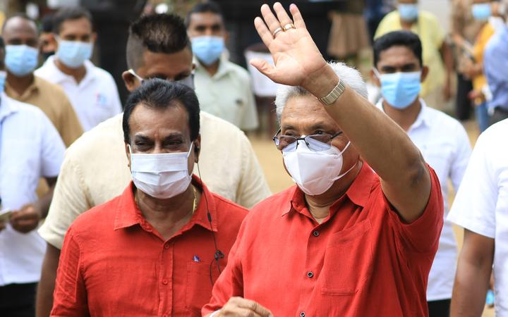 Sri Lankan president Gotabaya Rajapaksa wearing a face mask gestures as he leaves after casting his vote for the parliamentary election at a polling station in Colombo.