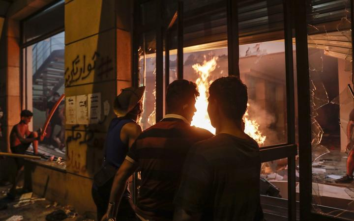 Lebanese protesters watch the flames inside the headquarters of the Lebanese association of banks in downtown Beirut on August 8, 2020,
