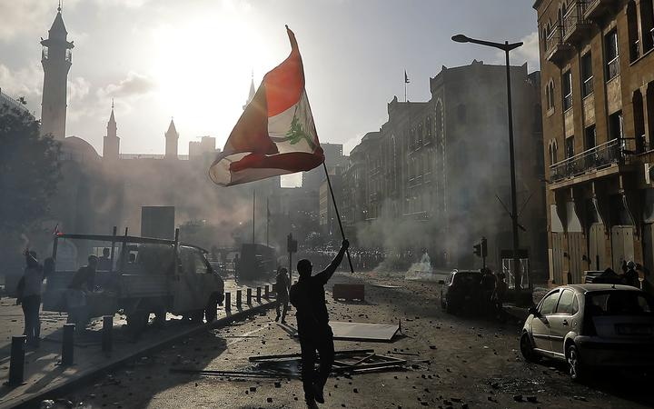 A Lebanese protester waves the national flag during clashes with security forces in downtown Beirut on August 8, 2020,