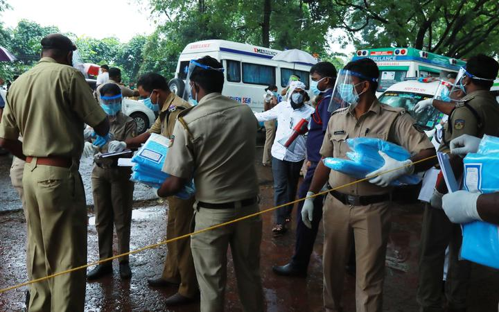 Police personnel distribute Personal Protective Equipment (PPE) kits amongst each other outside the medical college where Air India Express jet crash victims are taken for the post-mortem examination in Kozhikode, Kerala, on August 8, 2020.