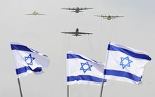 A new air force military cargo plane flies with Israeli military planes over Israeli flags in April 2014.